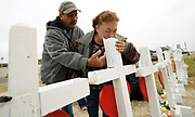 Lorenzo Flores (L) watches Terrie Smith kiss a cross placed in remembrance of those killed in the shooting at the First Baptist Church of Sutherland Springs, Texas, U.S.  November 9, 2017.  REUTERS/Rick Wilking