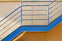 Blue staircase creates abstract lines against yellow and white wall