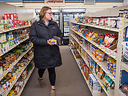 """25 FEBRUARY 2020 - BUTTERFIELD, MINNESOTA: KATIE HENDERSON, from St. James, MN., walks through the grocery section of the Butterfield True Value hardware store. She works in the Butterfield Post Office and came into the True Value to get some butter. Butterfield, MN, a farming community of about 500 people 130 miles southwest of the Twin Cities. The town has been a """"food desert"""" for 10 years after its only grocery store closed in 2010. Barb Mathistad Warner and Mark Warner purchased the True Value store in Butterfield in December, 2018 and started selling groceries in the store in May, 2019. For residents of Butterfield going to a grocery store meant driving 10 miles to St. James, MN, or 20 miles to Windom, MN, the two nearest communities with grocery stores. The USDA defines rural food deserts as having at least 500 people in a census tract living 10 miles from a large grocery store or supermarket. There is a convenience store in Butterfield, but it sells mostly heavily processed, unhealthy snack foods that are high in fat, sugar, and salt.   PHOTO BY JACK KURTZ"""