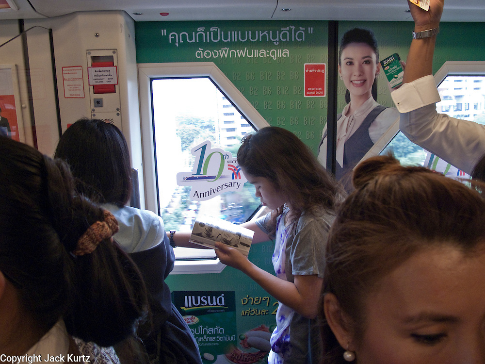 "09 OCTOBER 2009 -- BANGKOK, THAILAND: A student reads on the Sukhumvit line of the Bangkok ""Skytrain,"" BTS system. PHOTO BY JACK KURTZ"