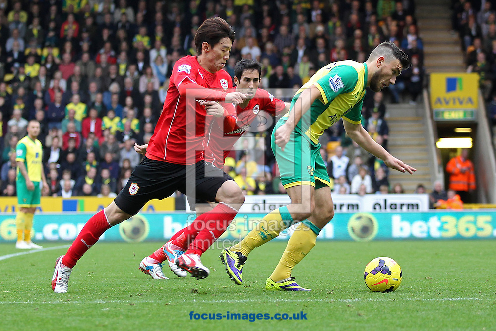 Picture by Paul Chesterton/Focus Images Ltd +44 7904 640267<br /> Robert Snodgrass of Norwich and Mim Bo-Kyung of Cardiff in action during the Barclays Premier League match at Carrow Road, Norwich.