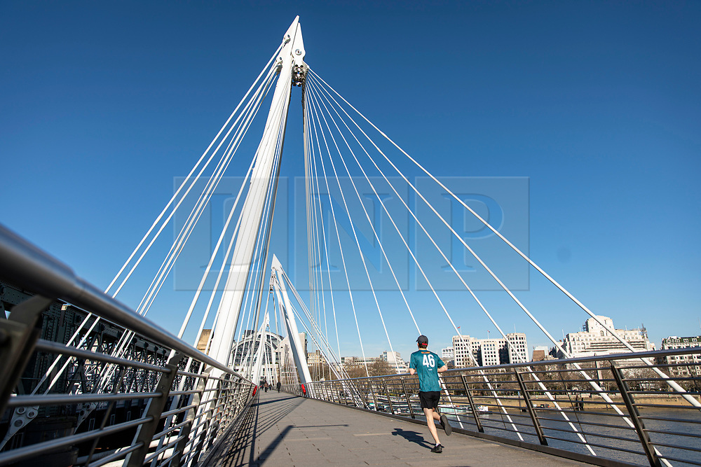 © Licensed to London News Pictures. 23/03/2020. London, UK. A runner crosses the Golden Jubilee Bridge as people continue to avoid central London. The government has refused to rule out tougher measures to enforce social distancing if people do not begin following the health advice. Photo credit: Rob Pinney/LNP