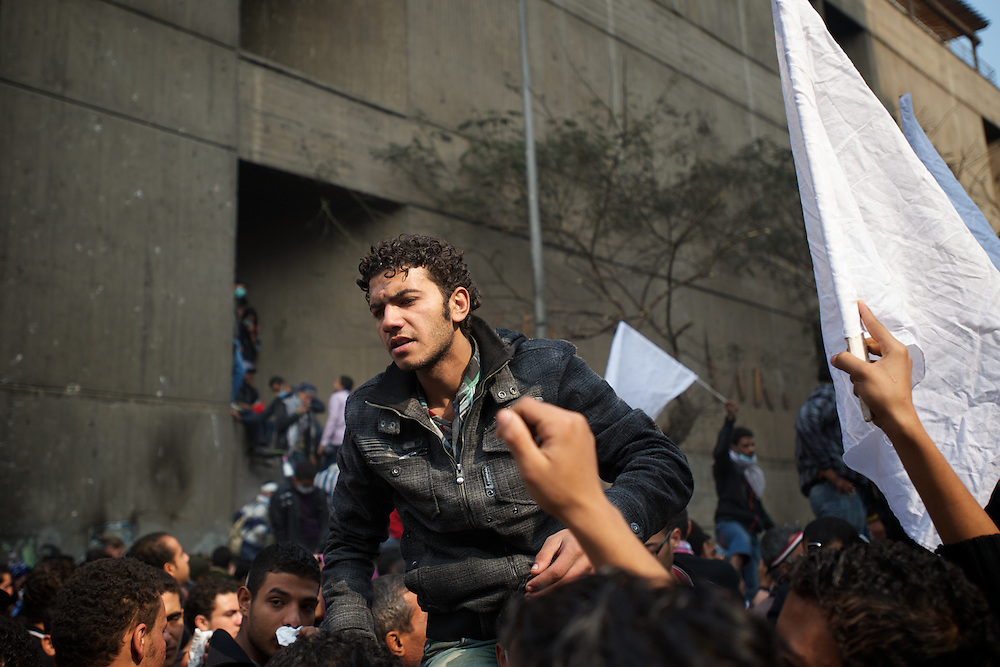 A young man tries to calm down a group of protestors during a speech by an army official in a road near a Ministry building in central Cairo.