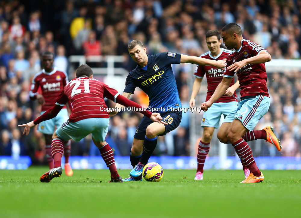 25 October 2014 - Barclays Premier League - West Ham v Manchester City - Edin Dzeko of Manchester City in action with Morgan Amalfitano and Winston Reid of West Ham - Photo: Marc Atkins / Offside.