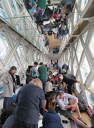 © Licensed to London News Pictures. 23/04/2017. LONDON, UK.  Member son the public watch marathon runners cross Tower Bridge, seen from the glass walkway of Tower Bridge, as runners reach the half way point.  Photo credit: Graham Long/LNP