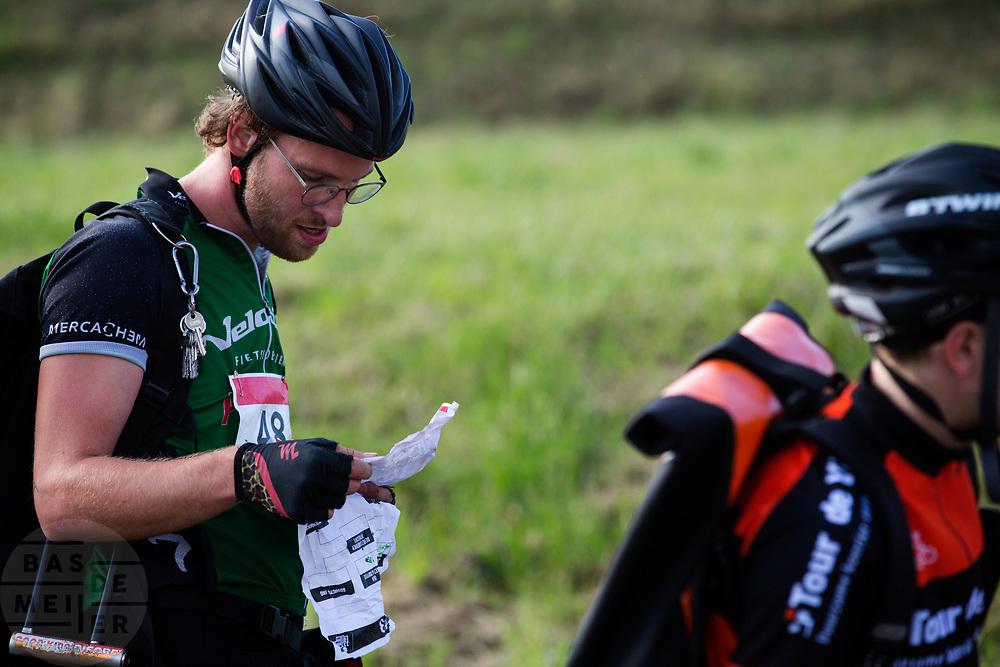 Een koerier bekijkt zijn manifest. In Nieuwegein wordt het NK Fietskoerieren gehouden. Fietskoeriers uit Nederland strijden om de titel door op een parcours het snelst zoveel mogelijk stempels te halen en lading weg te brengen. Daarbij moeten ze een slimme route kiezen.<br /> <br /> A messenger is looking at his manifest. In Nieuwegein bike messengers battle for the Open Dutch Bicycle Messenger Championship.