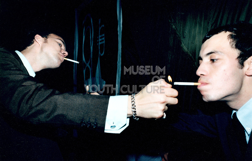 Two young men lighting each other's cigarettes.