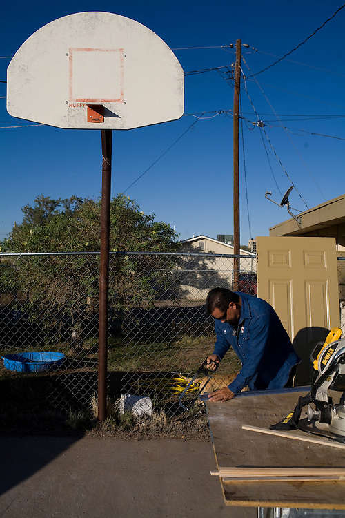 Joe Tarango works on weatherizing a home.  He works for the Community Action Agency(CAA). The CAA received stimulus funding and, among other things, works on weatherizing the homes of poor families and individuals in New Mexico.