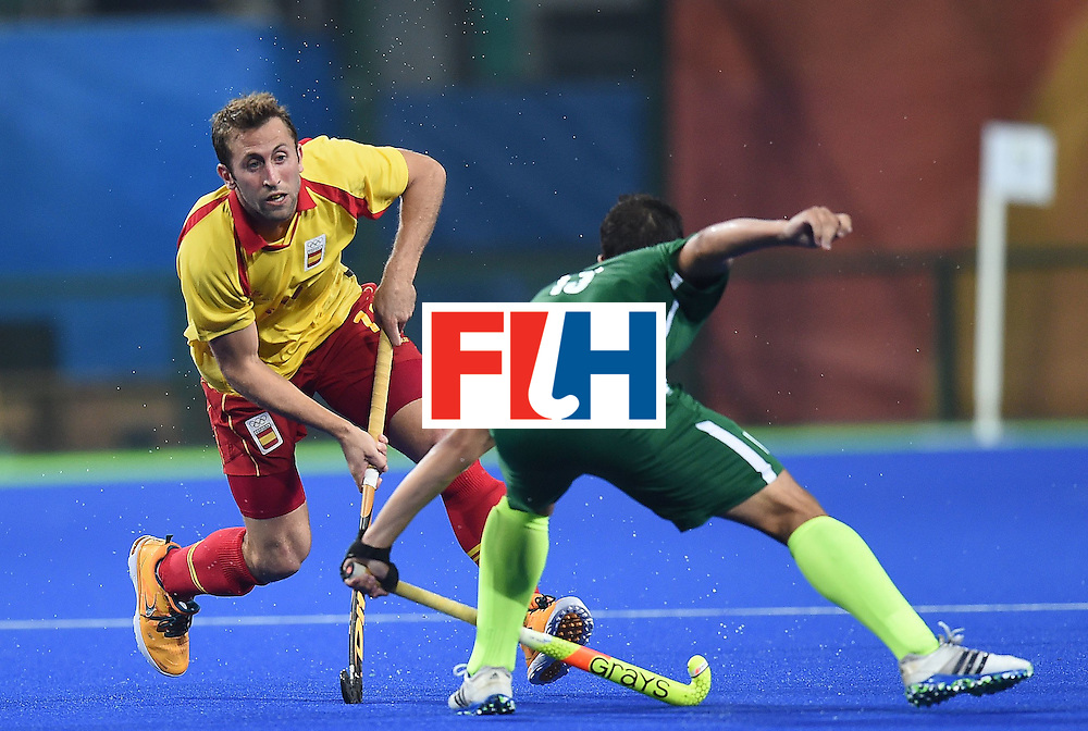 Spain's Roc Oliva fights for the ball with Brazil's Bruno Bitencourt during the men's field hockey Spain vs Brazil match of the Rio 2016 Olympics Games at the Olympic Hockey Centre in Rio de Janeiro on August, 6 2016. / AFP / MANAN VATSYAYANA        (Photo credit should read MANAN VATSYAYANA/AFP/Getty Images)