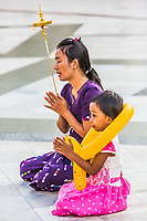 YANGON, MYANMAR - DECEMBER 16, 2016 : woman and her child praying at Shwedagon Pagoda Yangon (Rangoon) in Myanmar (Burma)