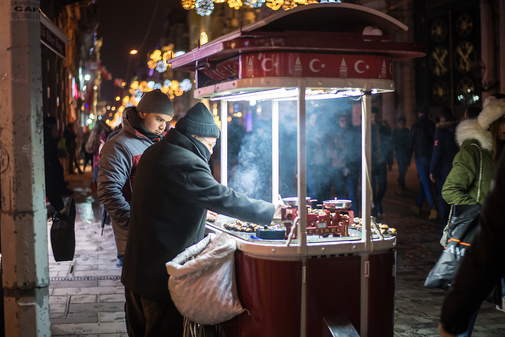 Two street vendors stand by food cart roasting chestnuts with fluorescent lights illuminated steam, Istanbul, Turkey
