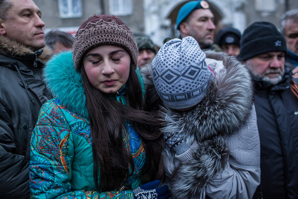 DONETSK, UKRAINE - JANUARY 24, 2015: Women hold back tears after embracing at a memorial event for victims of a rocket strike that hit a trolleybus two days earlier in Donetsk, Ukraine. The attack killed at least eight civilians and injured many more. CREDIT: Brendan Hoffman for The New York Times