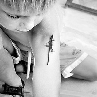A boy with a salamander on his arm at a wedding in Ibiza.