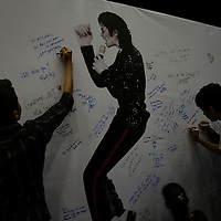 Fans write a messages on a poster during a tribute for pop star Michael Jackson at a shopping mall in Kuala Lumpur, Malaysia 28 June 2009.