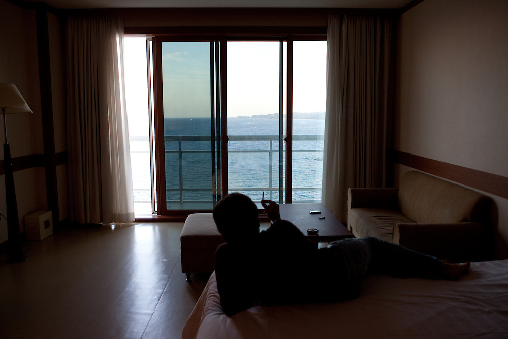 The woman tourist relaxing in the room with sea view at Hotel Palace / Samcheok, South Korea, Republic of Korea, KOR, 05 October 2009.