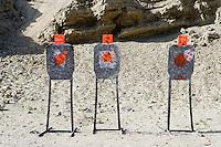 Three targets with bullet holes at firing range