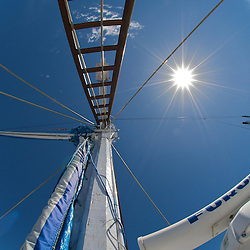 Wide angle shot of a ships mast construction against the sun.
