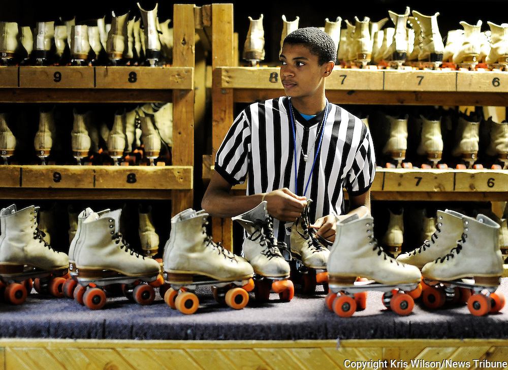 Kris Wilson/News Tribune<br /> Ricardo Finney steps away from his usual floor guard duties and helps check in skates at the rental counter following the last skate of the night during a Wednesday night &quot;cheap skate&quot; public session at Sk8 Zone.