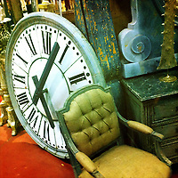 A giant watch among other items in an antiques shop.