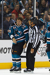 Feb 8, 2012; San Jose, CA, USA; NHL linesman Jay Sharrers (57) escorts San Jose Sharks center Andrew Desjardins (69) to the penalty box after a fight with Calgary Flames defenseman Cory Sarich (not pictured) during the second period at HP Pavilion. Mandatory Credit: Jason O. Watson-US PRESSWIRE
