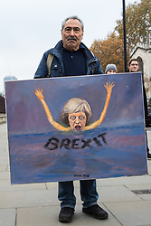 London, UK. 15th November, 2018. Satirical artist Kaya Mar poses with one of his paintings outside the House of Commons following the Cabinet resignations of Brexit Secretary Dominic Raab and Work and Pensions Secretary Esther McVey the day after Prime Minister gained Cabinet approval of a draft of the final Brexit agreement