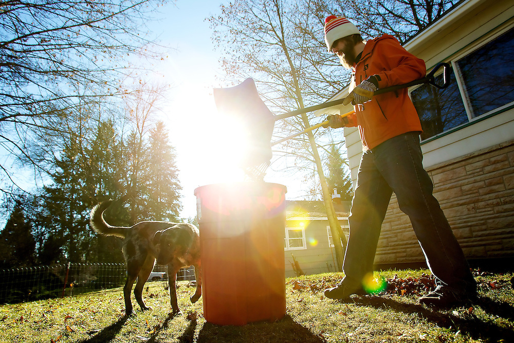 Lars Johansson dumps leaves into a garbage can Monday as he rakes his front yard on Government Way in Coeur d'Alene with his dog. The sunny weather and lack of snow motivated people to get outdoors despite the subfreezing temperatures.