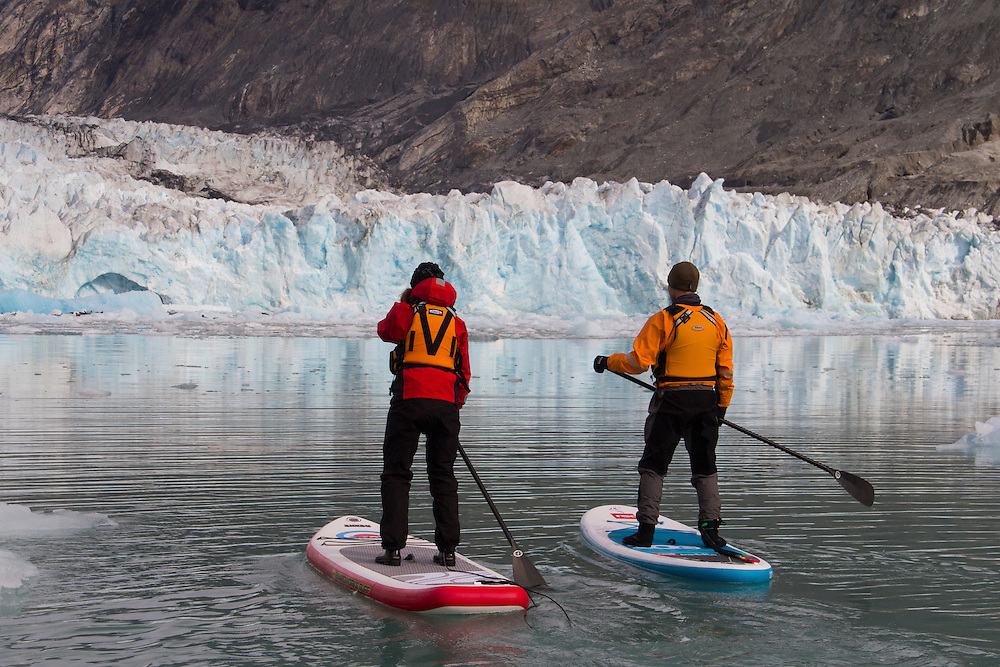 Two stand up paddle boarders (SUP) approach the McBride Glacier. MR