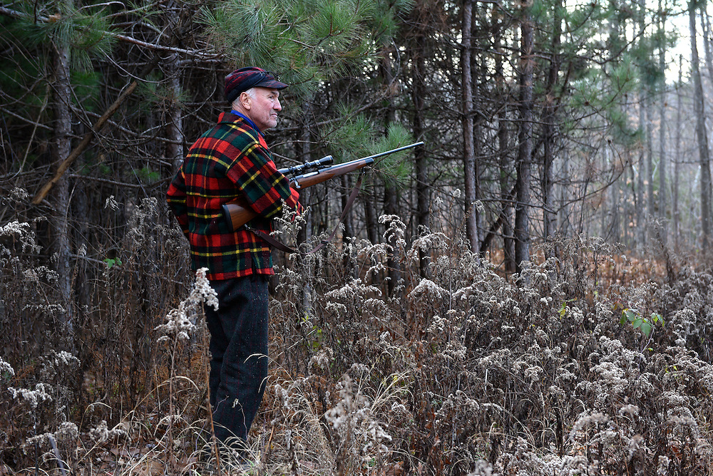 Bernie Corrette, of Lebanon, pauses to load his rifle on his way into the woods to hunt in Lebanon, N.H. Tuesday, November 24, 2015.  (Valley News - James M. Patterson)<br />