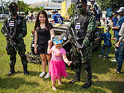 "14 JANUARY 2017 - BANGKOK, THAILAND: A Thai child and her mother walk past Thai Special Forces soldiers during Children's Day activities at the King's Guard, 2nd Cavalry Division base in Bangkok. Thailand National Children's Day is celebrated on the second Saturday in January. Known as ""Wan Dek"" in Thailand, Children's Day is celebrated to give children the opportunity to have fun and to create awareness about their significant role towards the development of the country. Many government offices open to tours and military bases hold special children's day events. It was established as a holiday in 1955.        PHOTO BY JACK KURTZ"