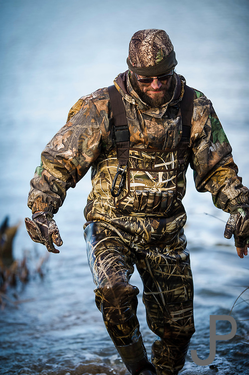 Dave Prather wades to shore after resetting decoys while duck hunting near Shamrock, Oklahoma