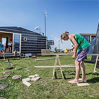 Nederland, Amsterdam, 4 mei 2016.<br /> Fab-city, expositie van allerlei duurzame initiatieven.<br /> Op de foto: Er wordt gewerkt en getimmerd aan het kleine huisje dat Tiny Tim heet.<br /> <br /> FabCity is een tijdelijke, gratis toegankelijke campus op de Kop van Java-eiland in het oostelijk havengebied van Amsterdam en bestaat uit zo'n vijftig innovatieve paviljoens, installaties en prototypes. Meer dan vierhonderd jonge studenten, professionals, kunstenaars en creatieven ontwikkelen de plek tot een duurzaam stedelijk gebied, waar ze werken, creëren, onderzoeken en hun oplossingen voor stedelijke vraagstukken presenteren. De deelnemers komen van verschillende onderwijsachtergronden, zoals kunstacademies, (technische) universiteiten en het beroepsonderwijs.<br /> <br /> FabCity is a temporary and freely accessible campus open between 1 April until 26 June at the head of Amsterdam's Java Island in the city's Eastern Harbour District. Conceived as a green, self-sustaining city, FabCity comprises of approximately 50 innovative pavilions, installations and prototypes. More than 400 young students, professionals, artists and creatives are developing the site into a sustainable urban area, where they work, create, explore and present their solutions for current urban issues. The participants come from various educational backgrounds, including art and technology academics, universities and vocational colleges.<br /> <br /> source:http://europebypeople.nl/fabcity-2<br /> <br /> Foto: Jean-Pierre Jans