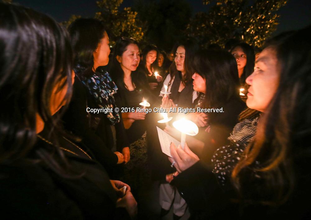 1月25日,美国洛杉矶县阿卡迪亚市,家长们手拿蜡烛参加在阿卡迪亚高中举办的烛光晚会悼念两名在家中被害身亡华裔兄弟。上星期五,美国华裔聚居的洛杉矶县阿卡迪亚市发生双尸凶杀案,2名华裔高中学生为15岁的林安东尼(Anthony Lin)和他的哥哥,16岁的林威廉(William Lin),怀疑被姑父在家中用钝器杀害,其后,杀害两兄弟的姑父搭乘国泰航空离开美国,但香港国际机场被当地警察逮捕。新华社发 (赵汉荣摄)<br /> Students hold a candlelight at Arcadia High School Monday night, January 25, 2016, during a candlelight vigil for the two brothers killed by their uncle in Friday, in Arcadia, California, the United States. Two brothers, 15 and 16, were found by their parents Friday at their home near school. They appeared to have suffered blunt force trauma and were pronounced dead at he scene, official said. They were identified as Arcadia High School students William and Anthony Lin, according to a statement from the Arcadia Unified School District. Their 44-year-old uncle, identified as Deyun Shi, who is suspected of killing the boys after becoming enraged that his wife had obtained a restraining order against him and begun divorce proceedings, fled on a plane to China, but was taken into custody by Hong Kong authorities Saturday as his plane arrived at Hong Kong International Airport, officials said. Authorities are working to have him returned to California. (Xinhua/Zhao Hanrong)(Photo by Ringo Chiu/PHOTOFORMULA.com)<br /> <br /> Usage Notes: This content is intended for editorial use only. For other uses, additional clearances may be required.