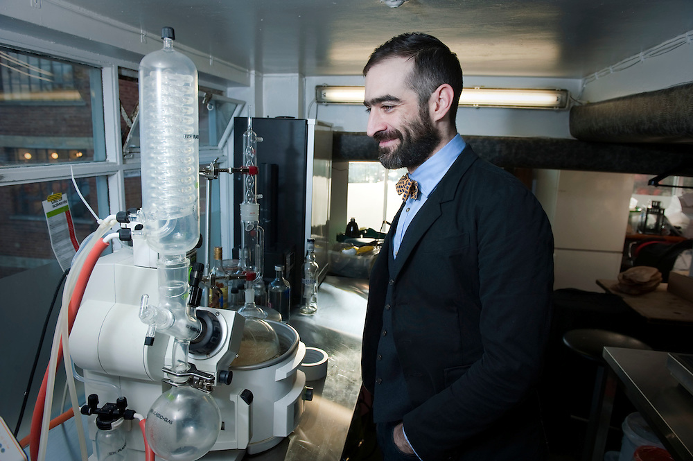 Tony Conigliaro, bartender who vacuum distills his own gin, with his vacuum distillation machine above his bar, 69 Colebrooke Row in Islington, London, UK.
