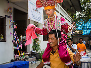 "04 APRIL 2015 - CHIANG MAI, CHIANG MAI, THAILAND:  A boy being ordained as a Buddhist novice dances during the Poi Sang Long Festival at Wat Pa Pao in Chiang Mai. The boys ride on men's shoulders during the festival because their feet aren't allowed to touch the ground. The Poi Sang Long Festival (also called Poy Sang Long) is an ordination ceremony for Tai (also and commonly called Shan, though they prefer Tai) boys in the Shan State of Myanmar (Burma) and in Shan communities in western Thailand. Most Tai boys go into the monastery as novice monks at some point between the ages of seven and fourteen. This year seven boys were ordained at the Poi Sang Long ceremony at Wat Pa Pao in Chiang Mai. Poy Song Long is Tai (Shan) for ""Festival of the Jewel (or Crystal) Sons.     PHOTO BY JACK KURTZ"