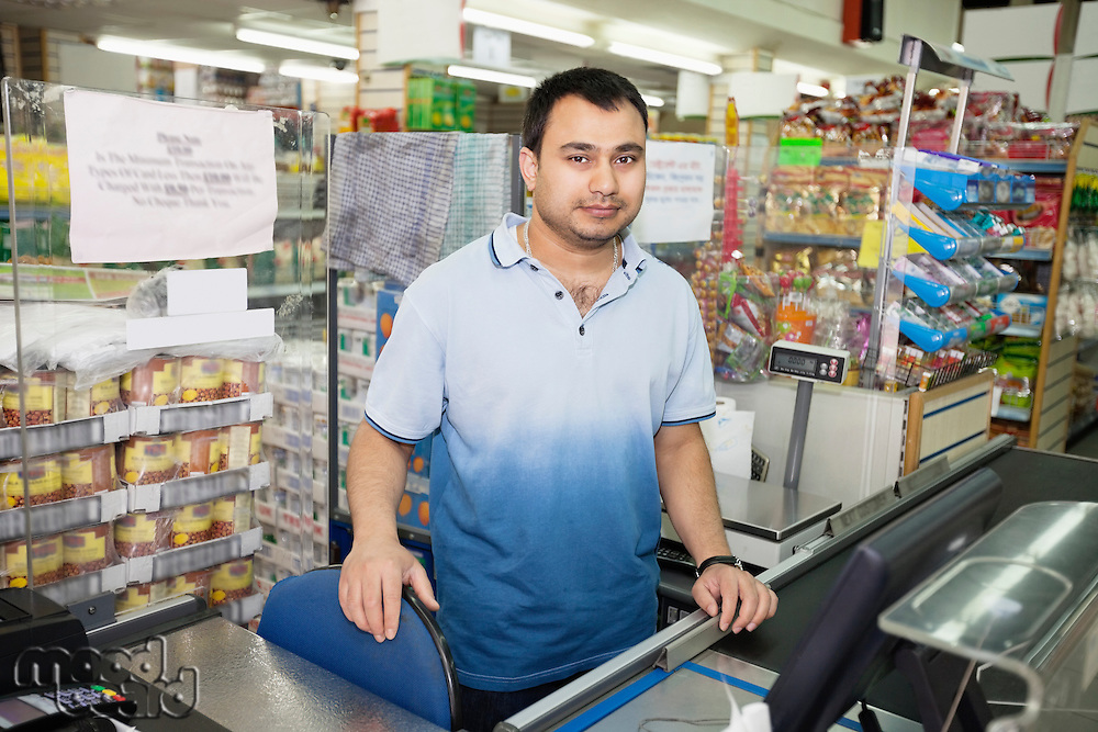 Portrait of male clerk standing at counter in grocery store