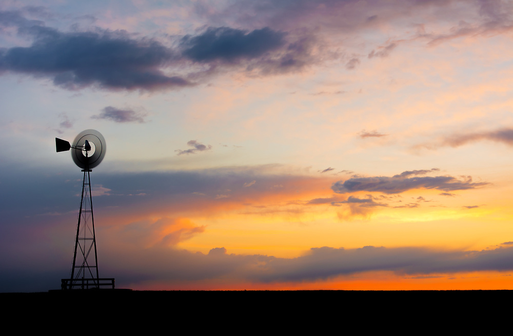 A picture of a windmill on the Colorado plains during sunset.<br />