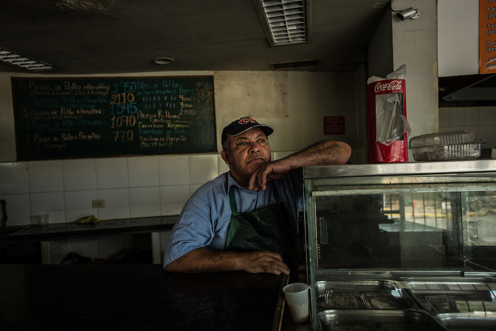 """CARACAS, VENEZUELA - MARCH 21, 2016: Fast food cook, Frank Almonte, waits in the restaurant where he works while the electricity was shut off during state-mandated rationing. Mr. Almonte said the rationing is bad for business, because he needs electricity to cook, food can go bad in the refridgerators, and customers leave without ordering when they learn they cannot pay with credit or debit cards because the machine used to process them needs electricity to work. Venezuela is shutting down this week, as the government struggles with a deepening electricity crisis.  President Nicolas Maduro gave everyone an extra three days off work, extending the two-day Easter holiday, according to a statement in the Official Gazette published late last Tuesday.  The government has rationed electricity and water supplies across the country for months and urged citizens to avoid waste as Venezuela endures a prolonged drought that has slashed output at hydroelectric dams. The ruling socialists have blamed the shortage on the El Nino weather phenomena and """"sabotage"""" by their political foes, while critics cite a lack of maintenance and poor planning.  PHOTO: Meridith Kohut for Bloomberg News"""