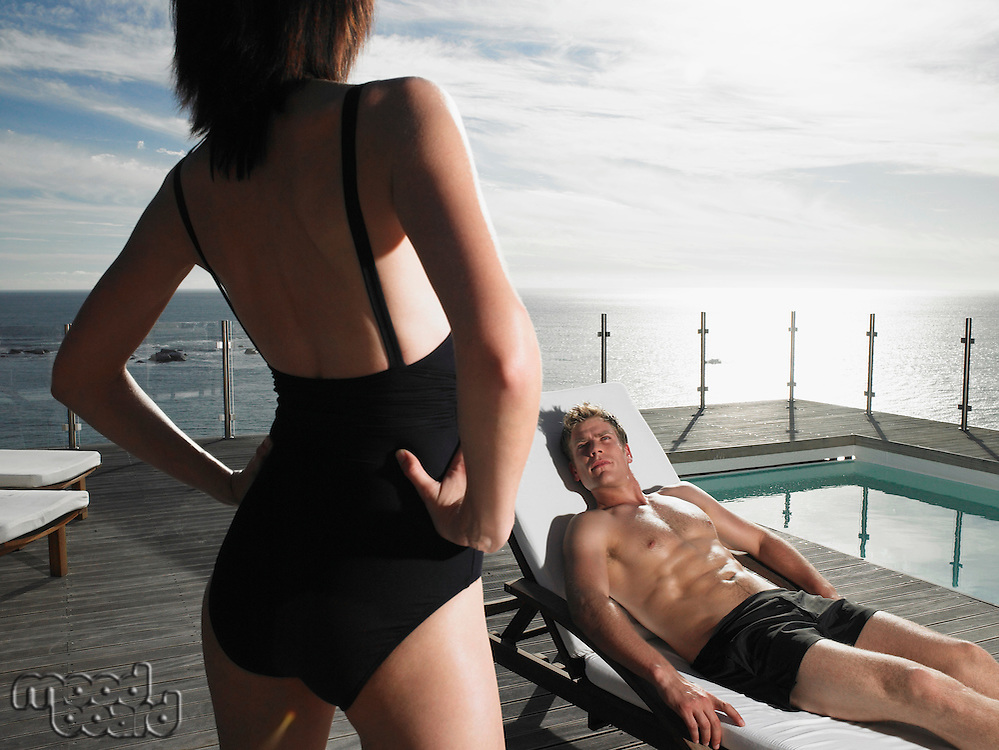 Man on a deck chair looking up at woman at pool by ocean