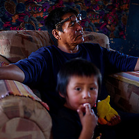 Andy Agoodi sits with his grandson Leandon Claw at their home near White Mesa on the former Bennett Freeze Wednesday.