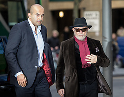 © Licensed to London News Pictures. 14/01/2015. London, UK. Former pop star, Gary Glitter (real name Paul Gadd) arrives with his bodyguard at Southwark Crown Court in London on 14 January 2015, accused of a number of sex offences against two girls. Glitter denied all the charges at a hearing last year. Photo credit : Vickie Flores/LNP