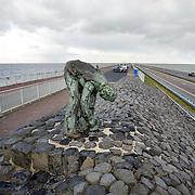 """Nederland Den Oever Zurich 22 november 2008 20081122 Foto: David Rozing ..Serie afsluitdijk. De Afsluitdijk is een belangrijke waterkering en verkeersweg in Nederland. De waterkering sluit het IJsselmeer af van de Waddenzee. Hieraan ontleent de dijk zijn naam. De verkeersweg, onderdeel van Rijksweg a7, verbindt Noord-Holland met Friesland...afsluitdijk ter hoogte van de uitkijktoren. Bronzen beeld Steenzetter.Ter gelegenheid van 50 jaar Afsluitdijk werd in 1982 het beeld de """"Steenzetter"""" van Ineke van Dijk geplaatst. Tekst: """" de strijd tegen het water blijft een strijd door en voor de mens """" Nederland Den Oever Zurich 22 november 2008 20081122 Foto: David Rozing ..Serie afsluitdijk. De Afsluitdijk is een belangrijke waterkering en verkeersweg in Nederland. De waterkering sluit het IJsselmeer af van de Waddenzee. Hieraan ontleent de dijk zijn naam. De verkeersweg, onderdeel van Rijksweg a7, verbindt Noord-Holland met Friesland...afsluitdijk ter hoogte van de uitkijktoren. Man bekijkt vanuit auto bronzen beeld Steenzetter.Ter gelegenheid van 50 jaar Afsluitdijk werd in 1982 het beeld de """"Steenzetter"""" van Ineke van Dijk geplaatst. Tekst: """" de strijd tegen het water blijft een strijd door en voor de mens """" standbeeld, monument, mensen, bezoekers  deltaplan...Foto David Rozing...Foto David Rozing/ Hollandse Hoogte"""
