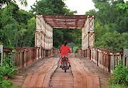 Stung Trang, Cambodia 062704  A woman crosses a bridge over a river. (Essdras M Suarez/ Globe staff)