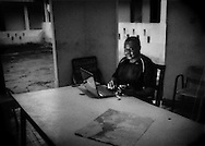Activist, Christopher Achobang working after a long day surveying the latest progress of the Herakles Farms oil palm/logging project at a local guesthouse.  Nguti, Cameroon.  Rural Southwest Cameroon offers up great logistical challenges.  <br /> <br /> The roads connecting the region to the rest of Cameroon are unpaved muddy quagmires in the rainy season.  In Southwest Cameroon, there is no electric power grid.  Most electricity is provided by gasoline-powered generator though this guesthouse provided enemic electricity, even during the rainy season, from an overburdened micro-hydroelectric generator.  Although there is simple mobile phone service, there is no internet service at all in the town, even though Christopher is attempting to use a portable modem and a smart phone.  There are public bush taxis to get around, though that means four adults sitting abreast in a compact Toyota Corolla, even in the front seat negotiating with a stick shift.  The most comfortable mode of short distance travel is on the back of Chinese-built motorcycle taxis.