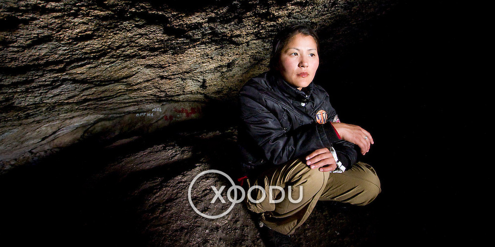 Young Mongolian woman crouches inside cave (Gorkhi-Terelj national park, Mongolia - Sep. 2008) (Image ID: 080917-1543121a)