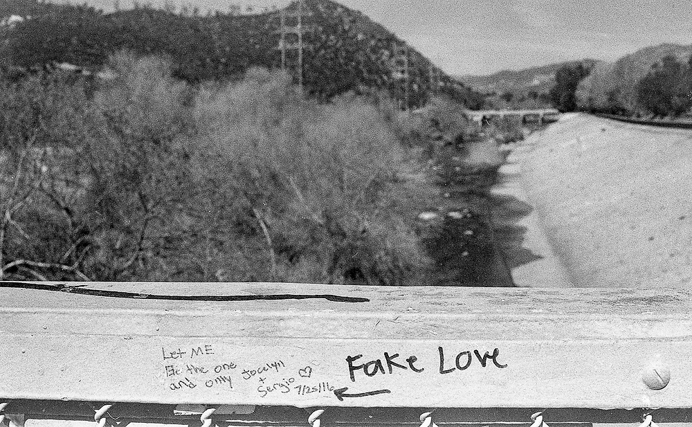 Black and white film photograph depicting Fake Love graffiti on a bridge overlooking the Los Angeles river, in Glendale, California
