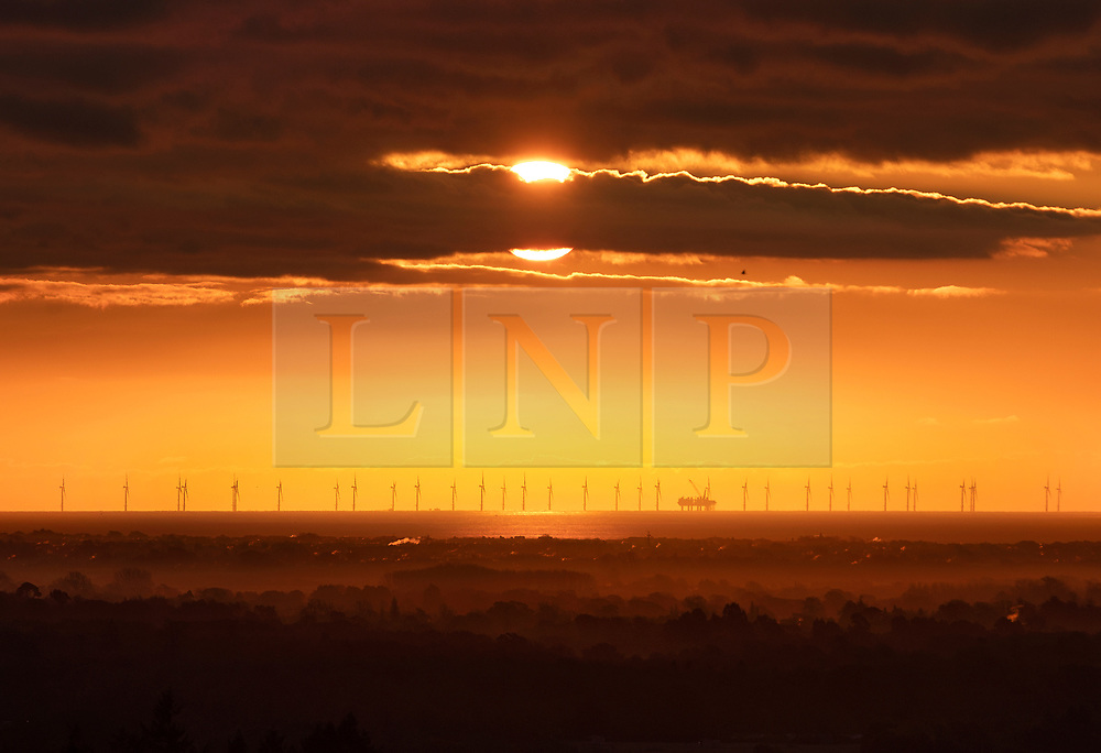 © Licensed to London News Pictures. 19/11/2019. Chichester, UK. Viewed from the South Downs, the morning sun rises above Rampion Wind Farm. Freezing temperatures and fog are hitting parts of the south. Photo credit: Peter Macdiarmid/LNP