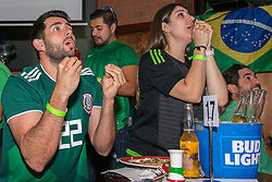 July 2, 2018 - FL, USA - Mexico fans Marcel Shorago and Christina Muniz react to a goal opportunity during FIFA World Cup Round of 16 knockout stage featuring Brazil versus Mexico at Vares in Brickell on Monday, July 2, 2018. (Credit Image: © Sam Navarro/TNS via ZUMA Wire)