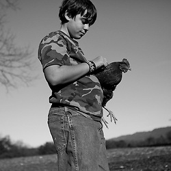 Kyle Green | The Roanoke Times<br /> 1/24/2012 Winston Palmer holds a family hen outside of his house in New Castle, Virginia. The family uses various means to get by in a tough economy, including growing their own herbs and vegetables, keeping chicken for eggs, and bartering goods for their artwork and services.