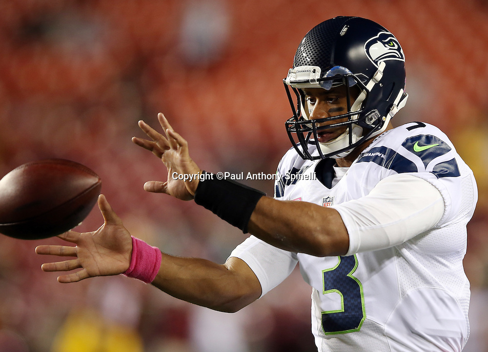 Seattle Seahawks quarterback Russell Wilson (3) catches a shotgun snap as he warms up before the NFL week 5 regular season football game against the Washington Redskins on Monday, Oct. 6, 2014 in Landover, Md. The Seahawks won the game 27-17. ©Paul Anthony Spinelli
