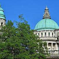 Dome of City Hall in Belfast, Northern Ireland<br /> The green copper dome of the Belfast City Hall is a prominent landmark. One layer of the Portland stone is supported by Ionic columns while the other is surrounded by balusters before reaching its 173 foot summit.  On the left is one of four corner towers.  The Baroque Revival design was created by Alfred Brumwell Thomas. Affectionately called the &ldquo;Wedding Cake,&rdquo; the City Council&rsquo;s building opened in 1906.